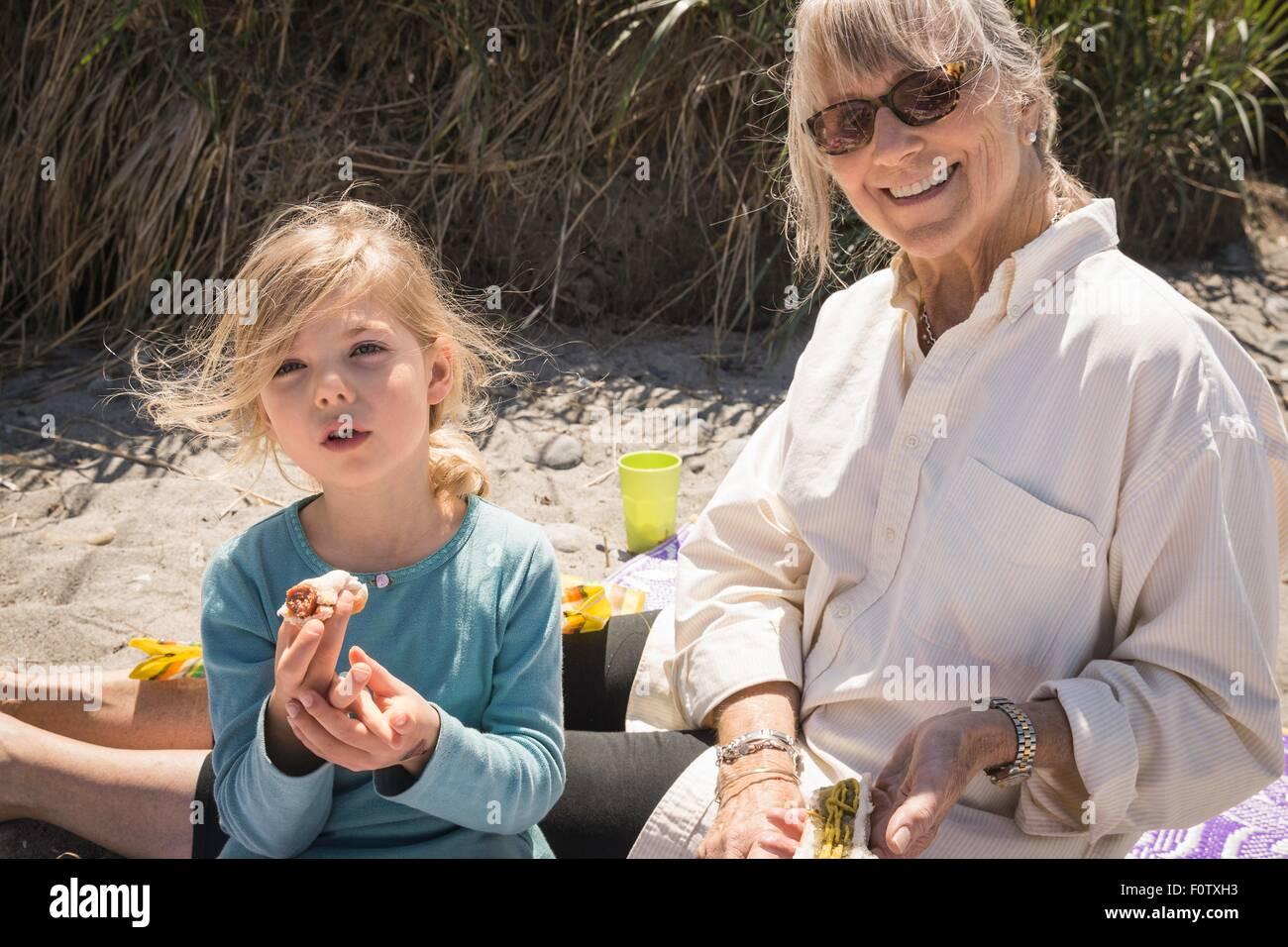 Großmutter und Enkelin mit Picknick am Strand Stockbild