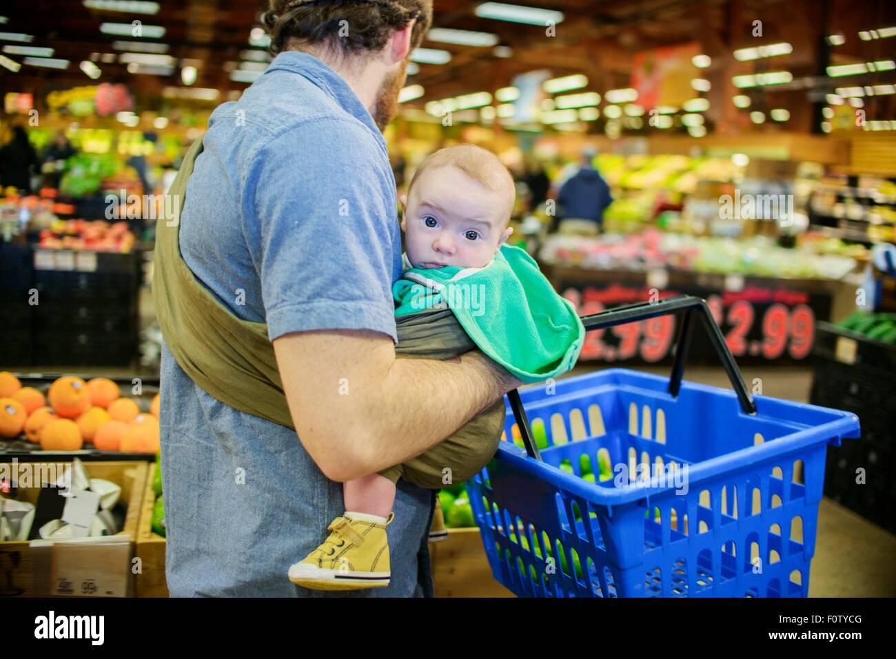 Vater Sohn halten und Einkaufswagen im Supermarkt Stockbild