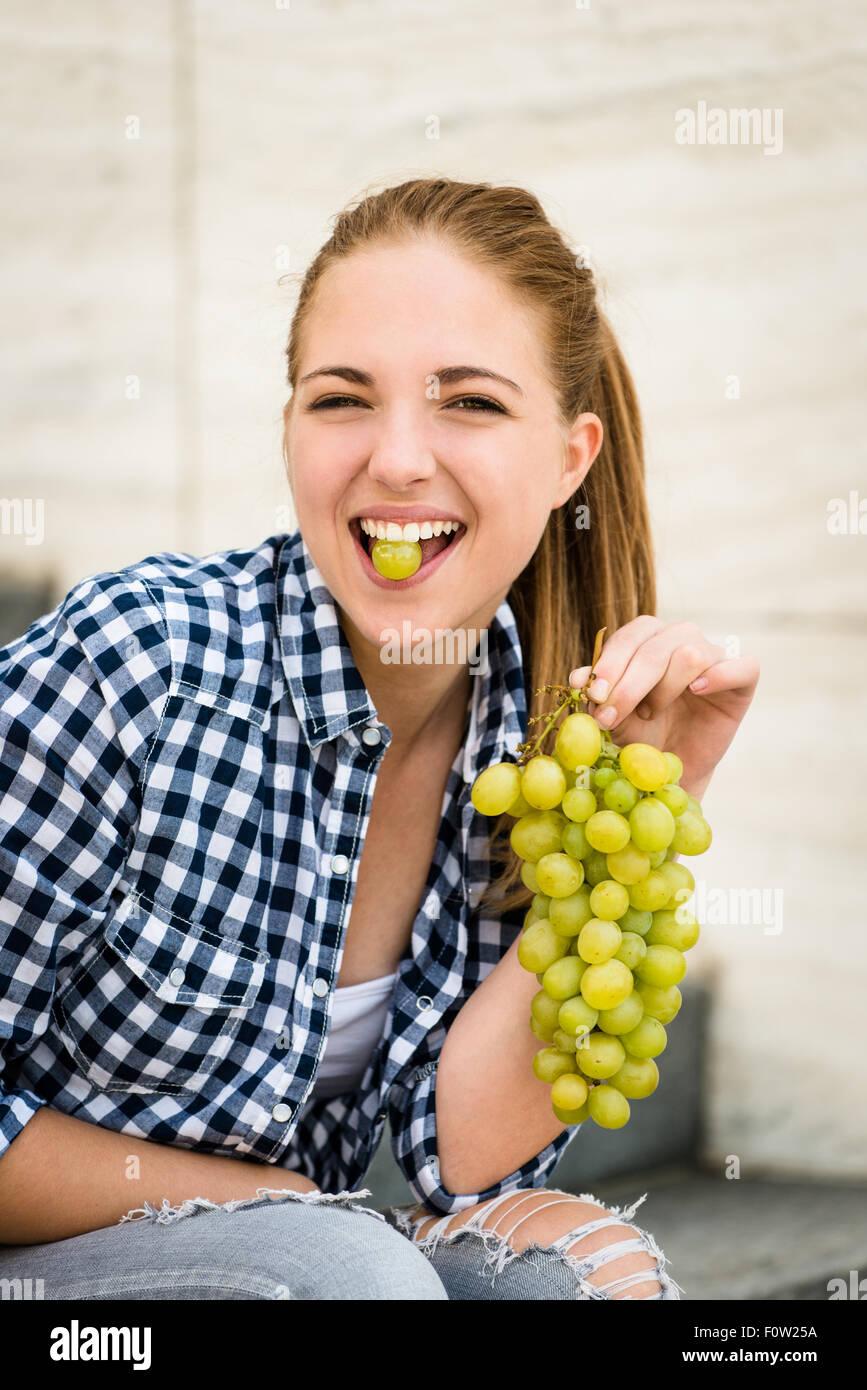 Junge Frau essen Trauben outdoor - Traube zwischen den Zähnen halten Stockbild