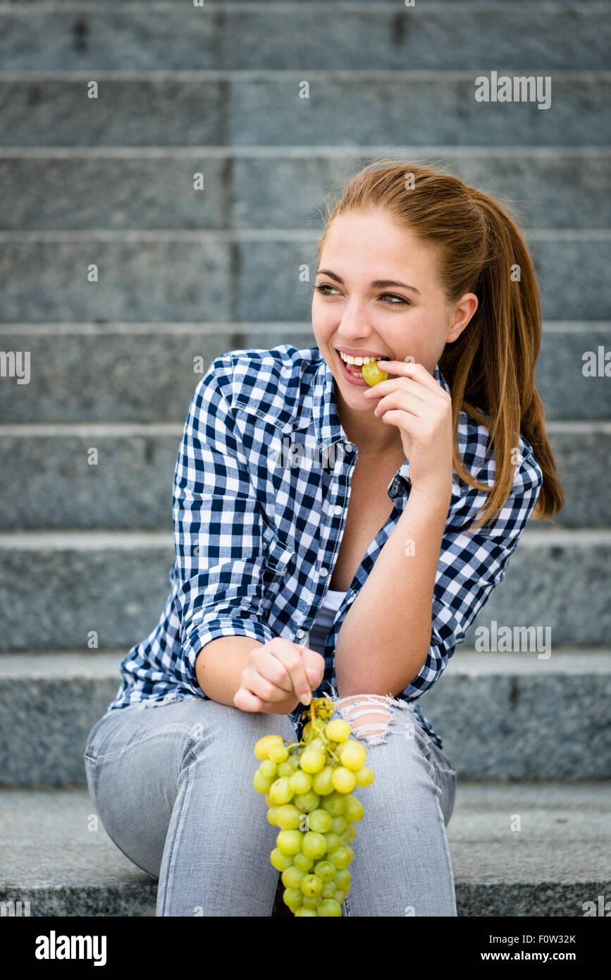 Junge Frau - Teenager-Mädchen essen Trauben im Freien sitzen auf Treppen Stockbild
