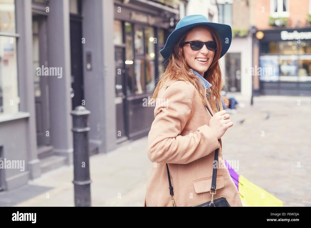 Porträt der stilvolle junge Frau auf der Suche über die Schulter, London, UK Stockbild