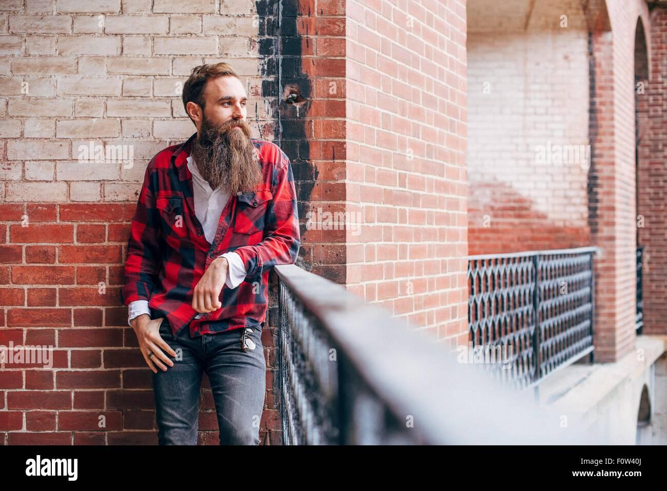 Mann mit Bart, stützte sich auf Balkon wegschauen Stockbild