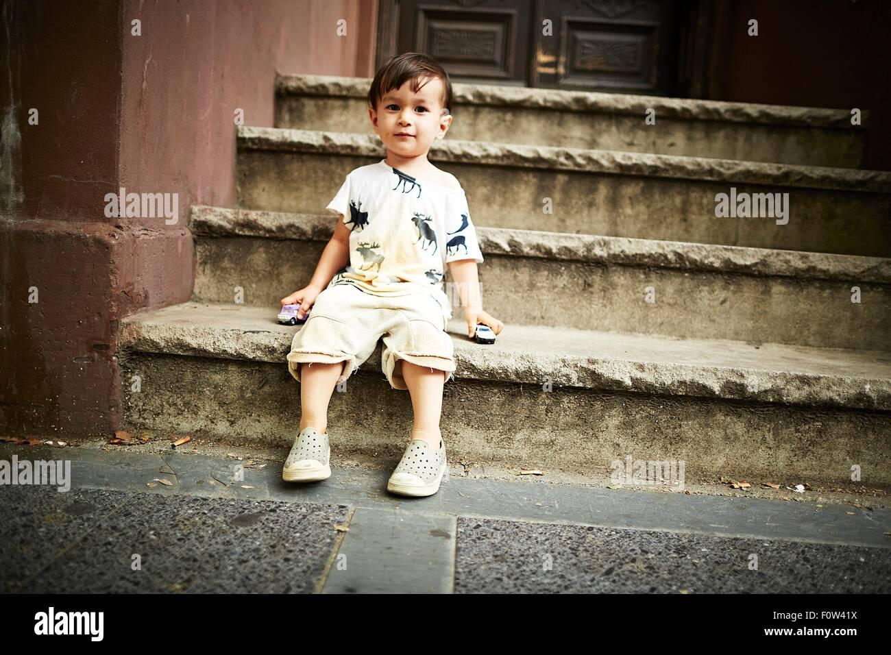 Junge sitzt auf Treppe Stockbild