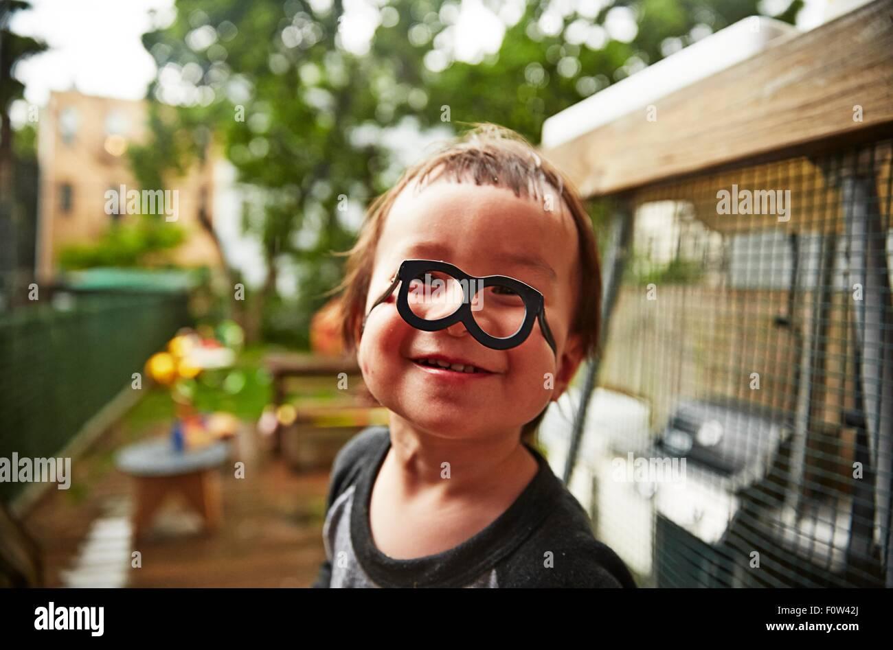 Junge mit lustigen Brillen im Garten Stockfoto