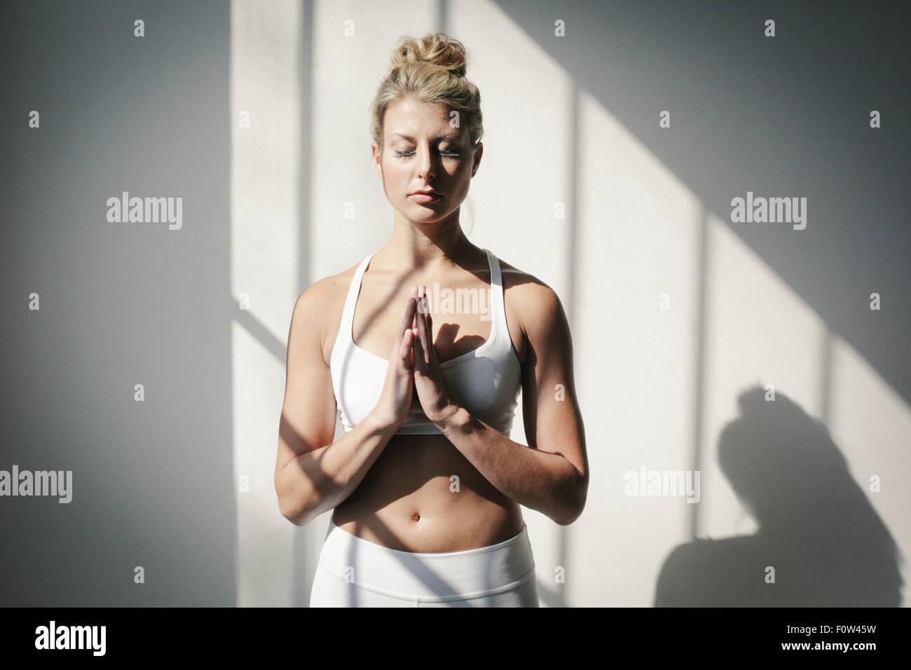 Eine blonde Frau, Augen geschlossen, in ein weißes bauchfreies Top und Leggings, steht man vor einer weißen Stockbild