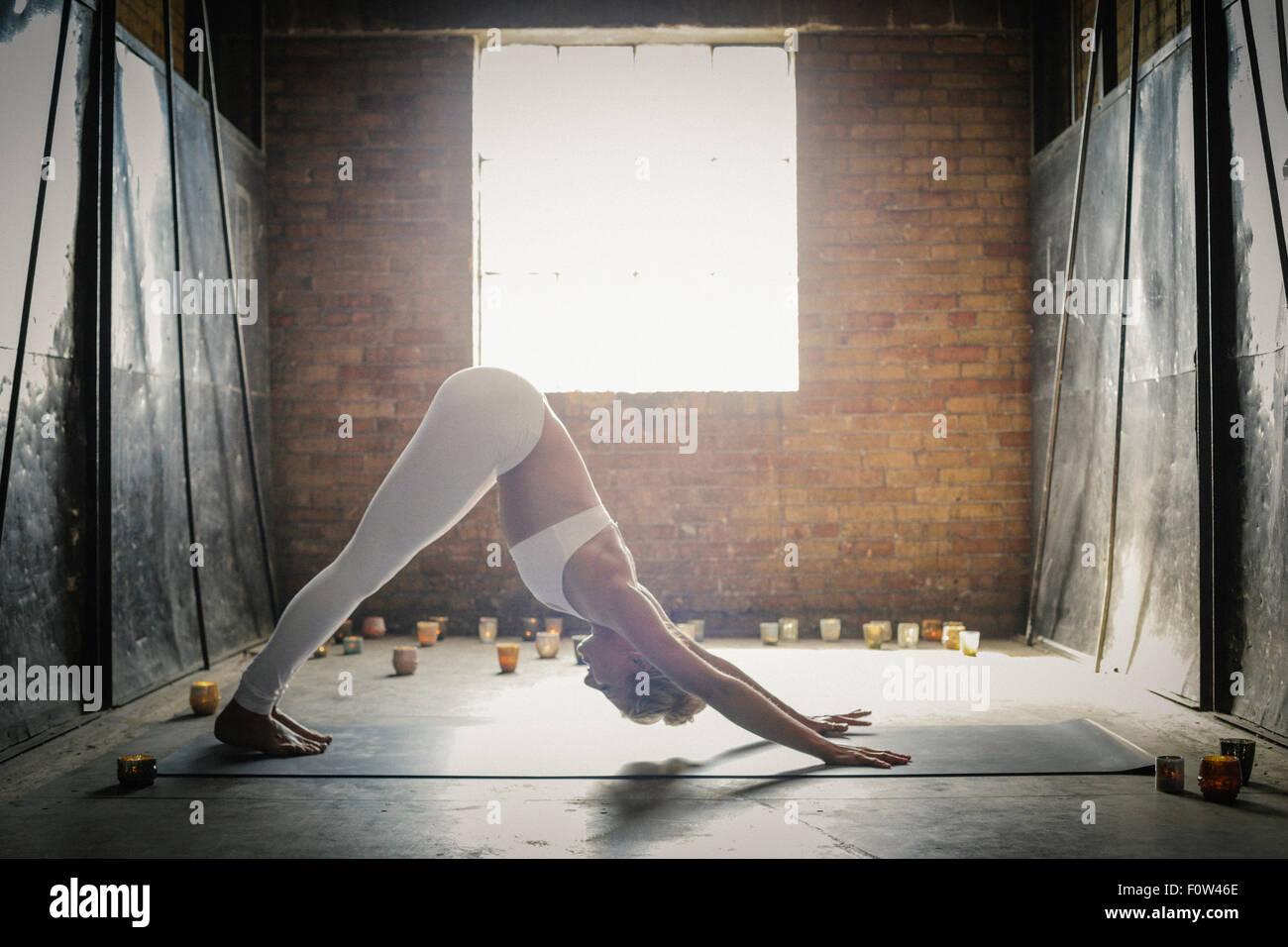 Eine blonde Frau auf dem Boden, umgeben von Kerzen, bücken dehnen. Ein Fenster in die Wand hinter ihr. Stockfoto