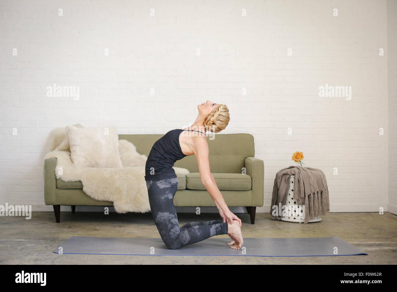 eine blonde frau kniend auf eine yoga matte in einem raum. Black Bedroom Furniture Sets. Home Design Ideas