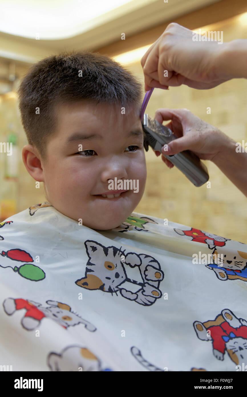 ein 7 jähriger Mischlinge junge immer eine Haar schneiden Stockfoto
