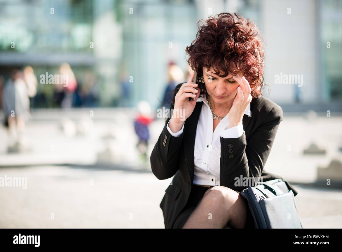 Senior Business-Frau mit Kopfschmerzen aufrufenden Telefon in der Straße im freien Stockbild