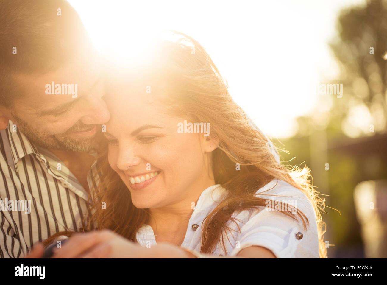 Glückliches Paar, tolle Zeit zusammen - bei Sonnenuntergang gegen die Sonne fotografiert Stockbild