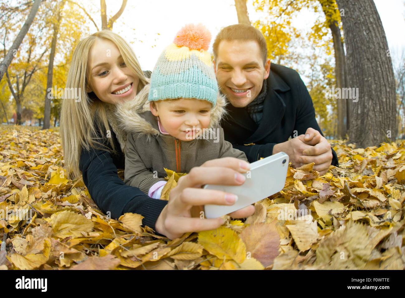 glückliche Familie mit Kleinkind nehmen Selfie am Telefon, im Herbst Park Ausflug Stockbild