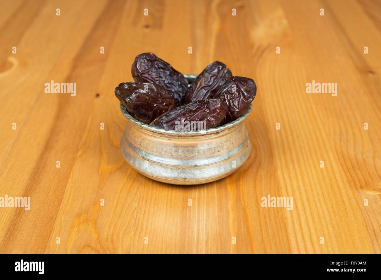 Schüssel mit getrocknete Datteln auf einem hölzernen Hintergrund Stockbild
