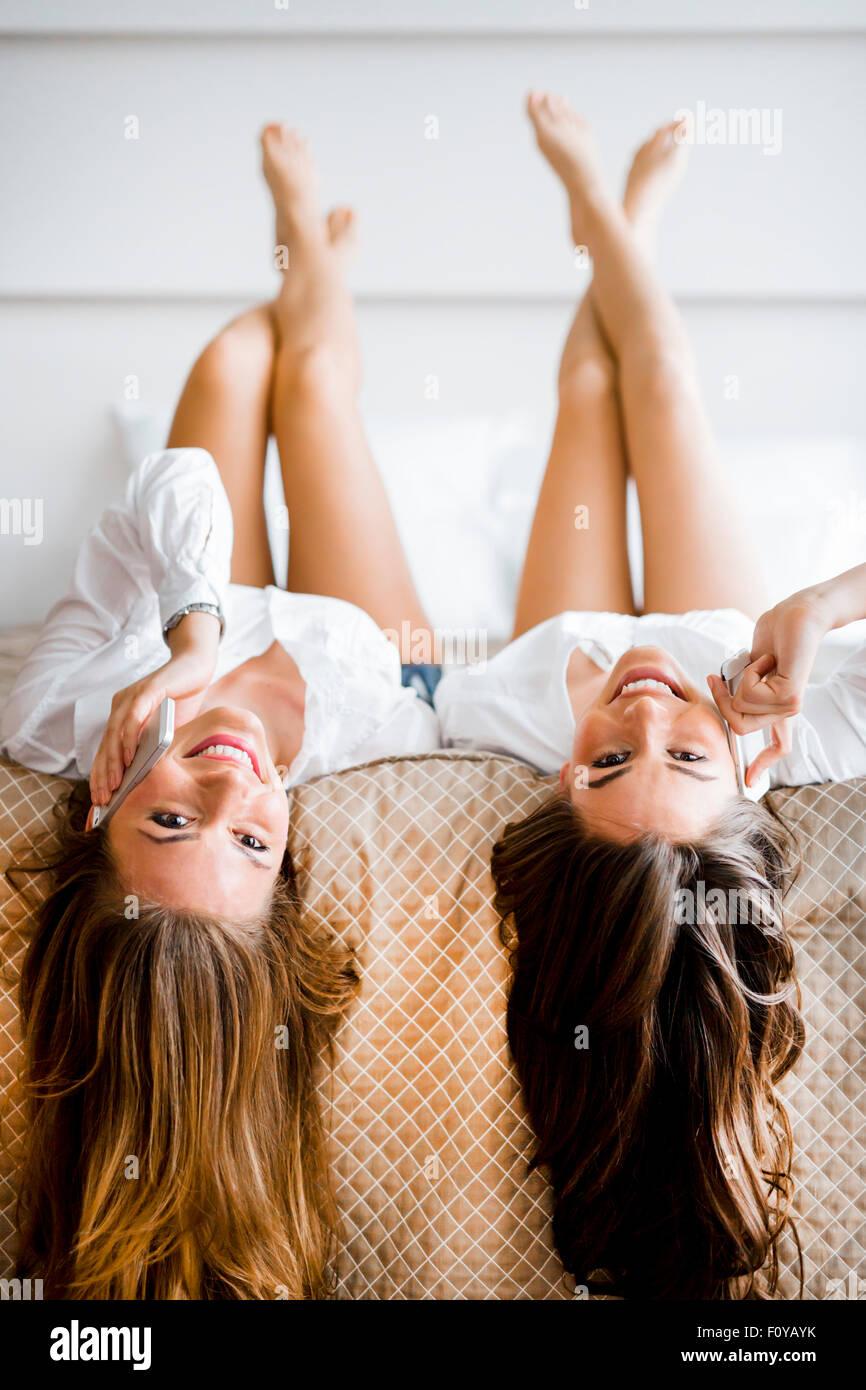 Zwei atemberaubende Frauen reden auf Handys mit ihren Haaren aus dem Bett fallen, wie sie kopfüber liegen Stockbild