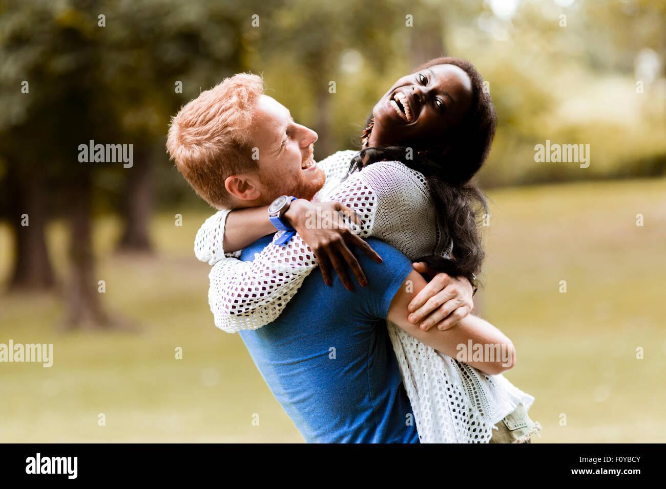 Porträt von einem glücklichen paar tanzen und umarmt in einem Park im freien Stockbild
