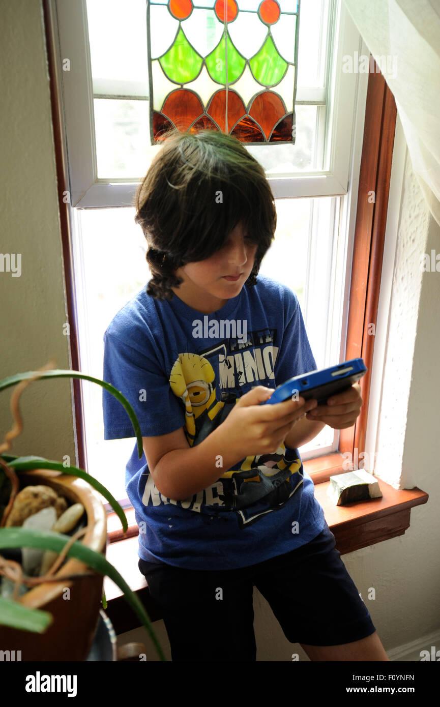 11 Jahre altes Mädchen spielen elektronische Spiel. Stockbild
