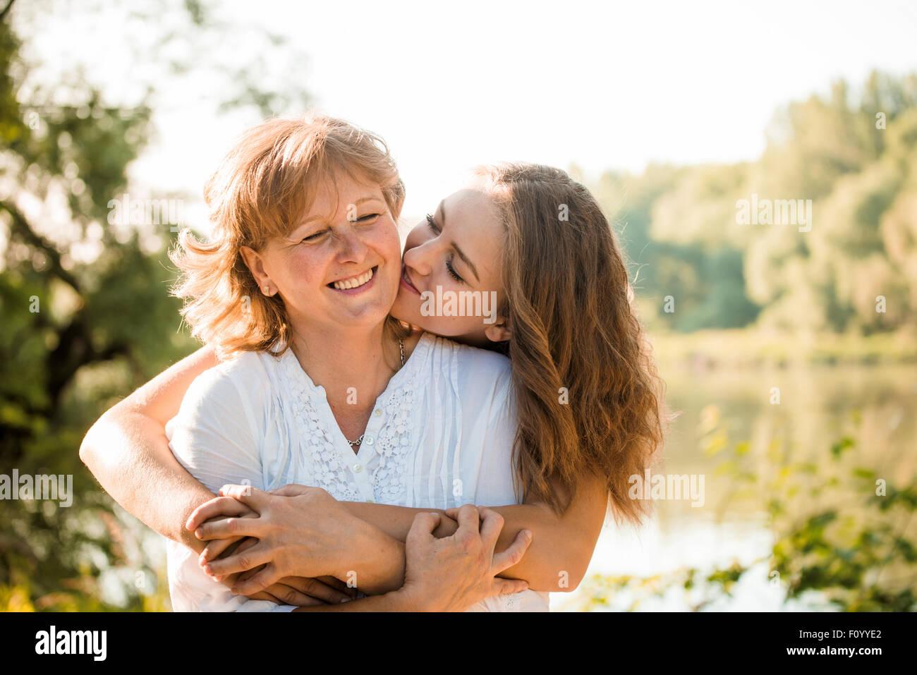 Reife Mutter umarmt mit Teen Tochter in der Natur im Freien an sonnigen Tag Stockbild