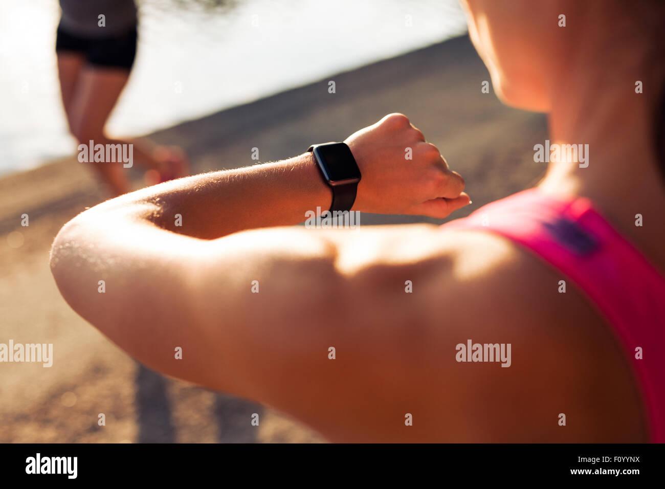 Shpt Sportlerin betrachten ihre Stoppuhr hautnah. Überprüfung auf ihre Smartwatch Jogger. Stockbild