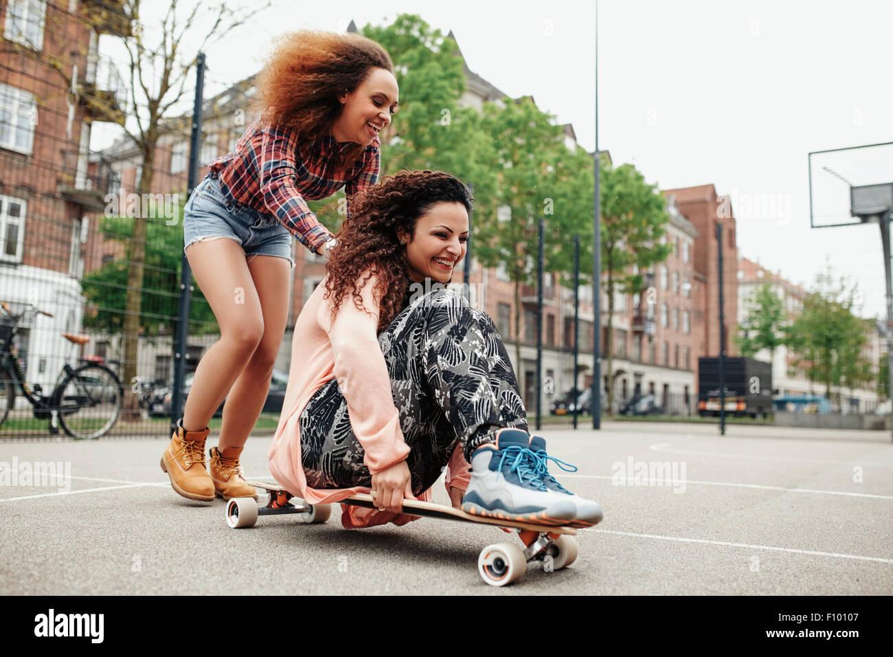 Fröhliches junges Mädchen sitzt auf Longboard von ihrer Freundin geschoben. Junge Frauen genießen, Stockbild