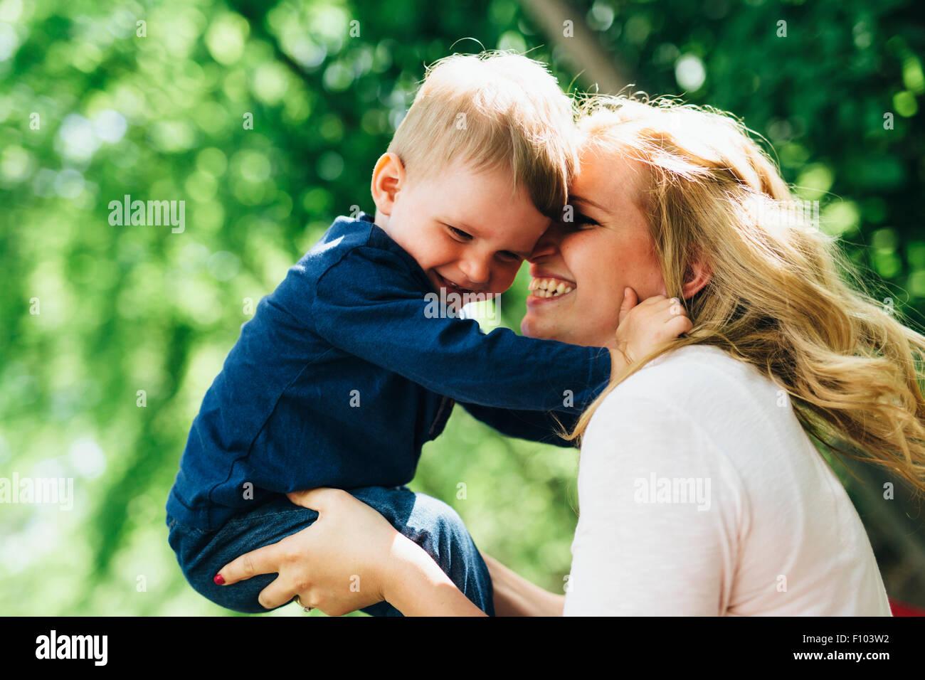 Mutter, Lächeln, lachen und spielen mit ihrem Kind im Freien an einem schönen Sommertag Stockbild
