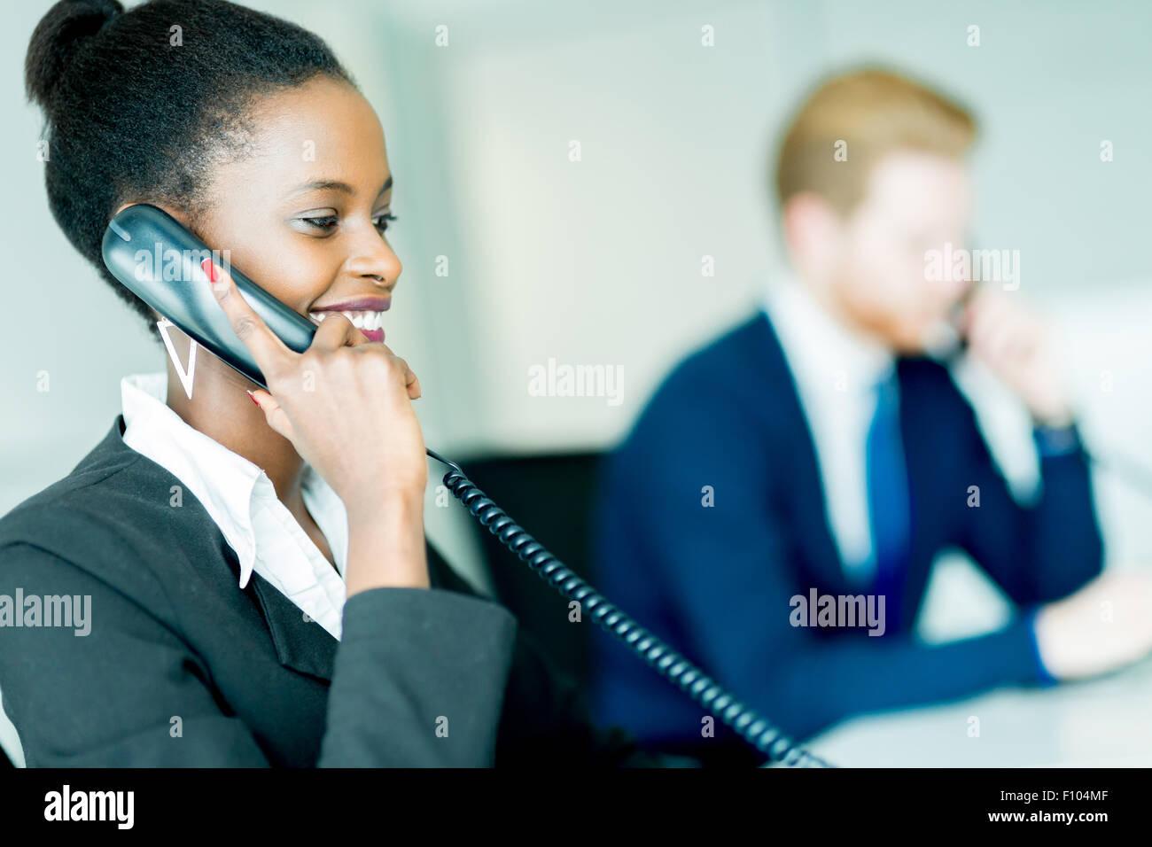 Eine schöne, schwarze, junge Frau arbeitet in einem Callcenter in einem Büro mit ihrem roten Haird Partner Stockbild