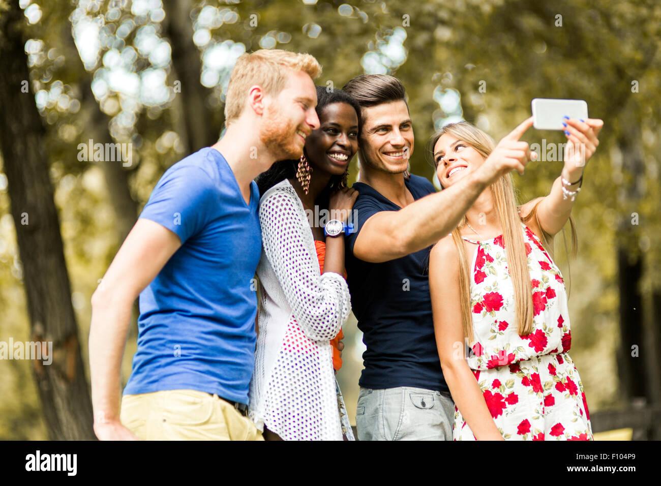 Gruppe von jungen Menschen und Paare unter Selfies in der Natur und lächelnd Stockbild