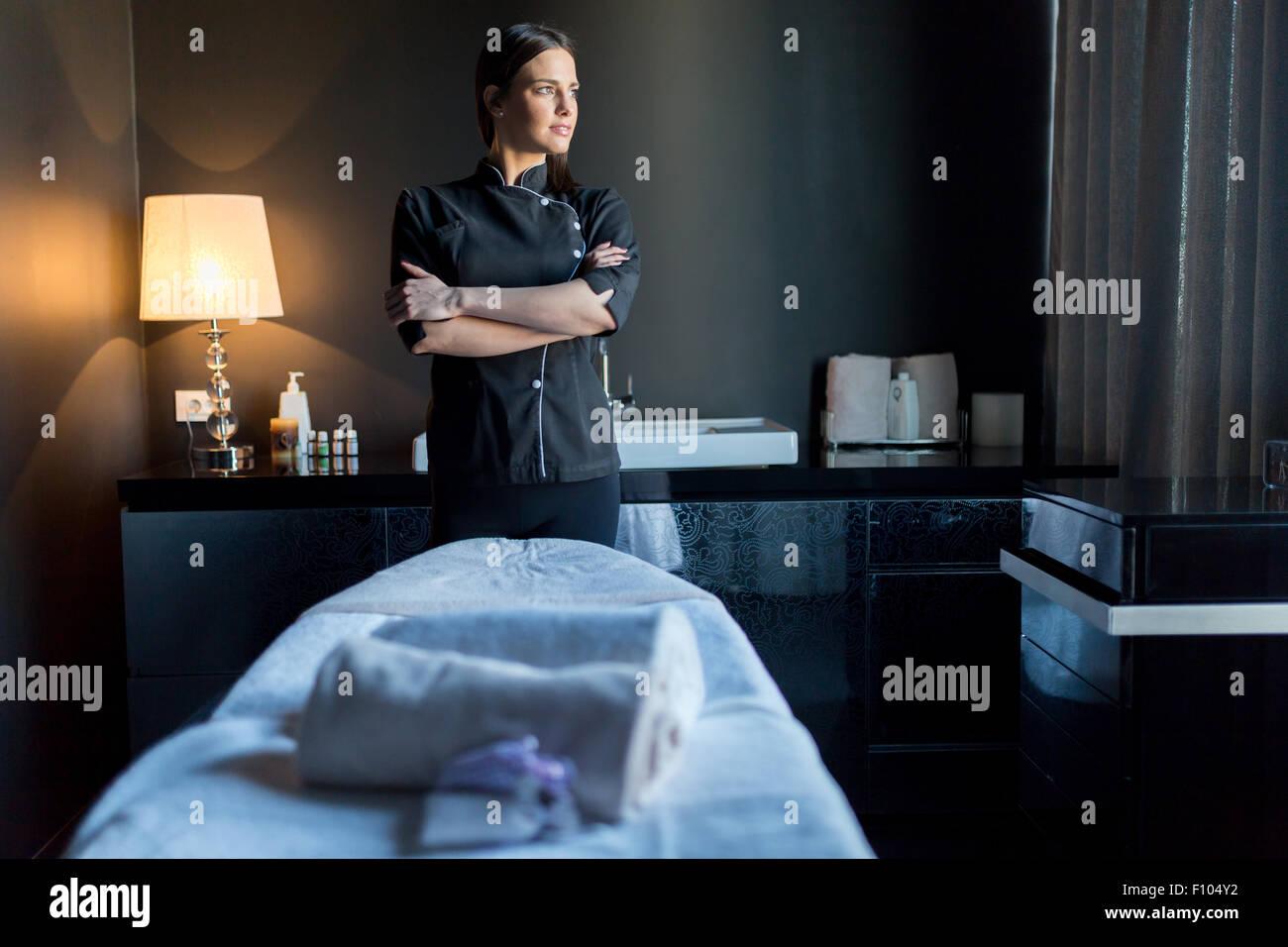 Massage-Therapeuten bereitzustehen Massagetisch mit Hände gekreuzt und auf der Suche nach draußen vor Stockbild