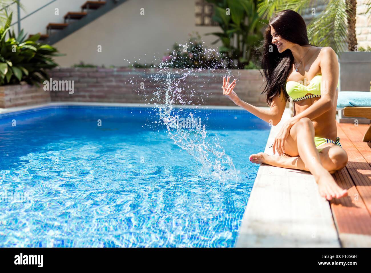 Junge schöne Frau an der Seite der Pool mit Wasser Anzeige Sinnlichkeit spielen Stockbild