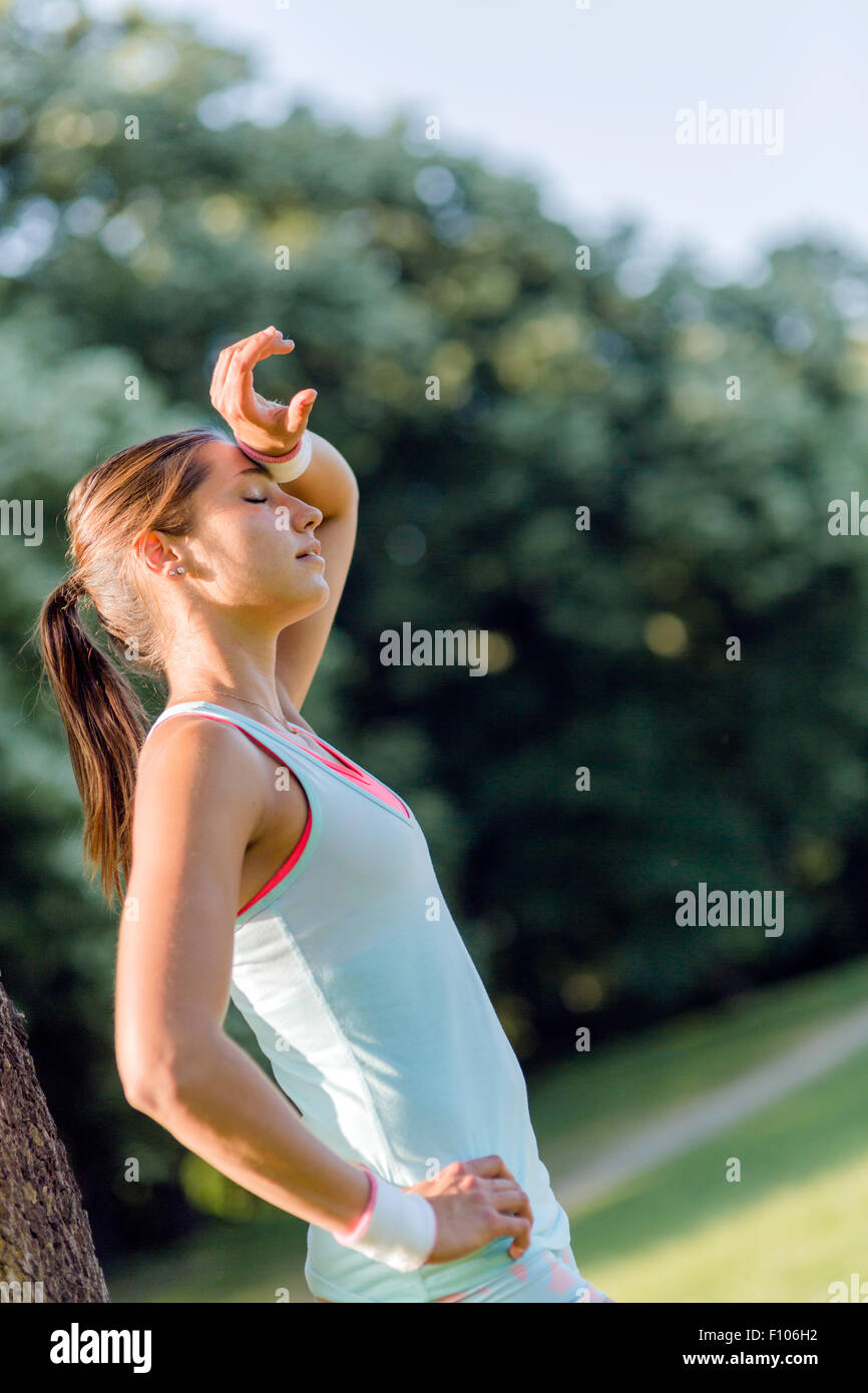 Junge Frau erschöpft nach sportlicher Betätigung in der Natur Stockbild