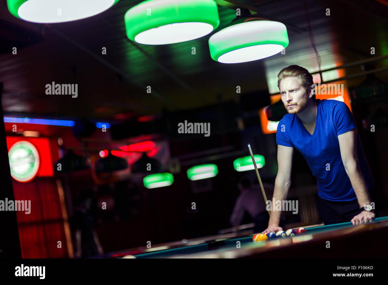 Hübscher Junge snooker Spieler beugte sich über den Tisch in einer Bar mit schönen Ambiente-Beleuchtung Stockbild