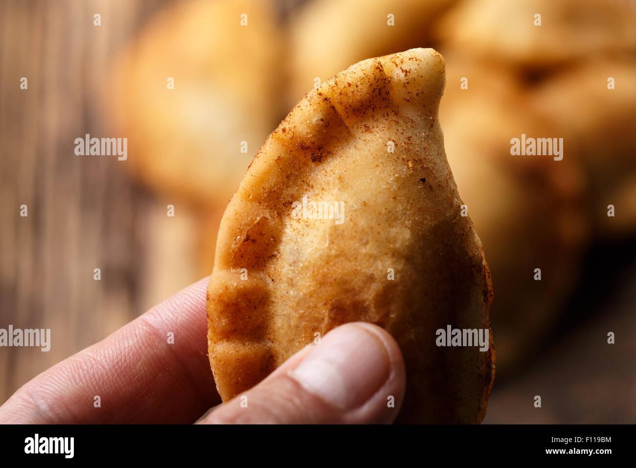 Männliche Hand mit gebratenen kolumbianische Empanada. Herzhafte gefüllte Pasteten, auch bekannt als Pastell, Stockbild