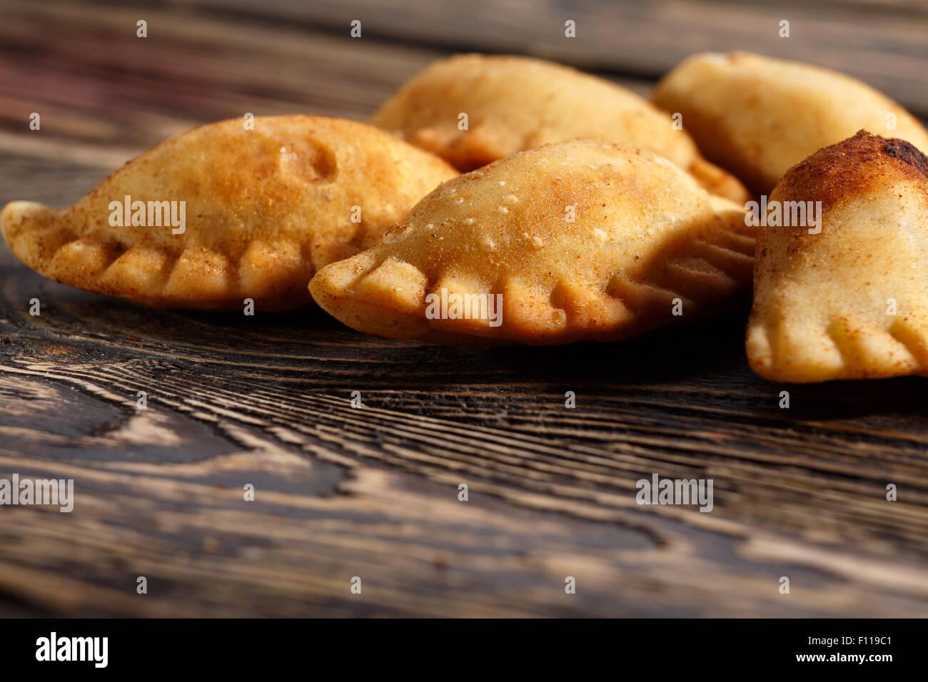 Fried kolumbianische Empanadas auf Holztisch. Herzhafte gefüllte Pasteten, auch bekannt als Pastell, Pastete Stockbild
