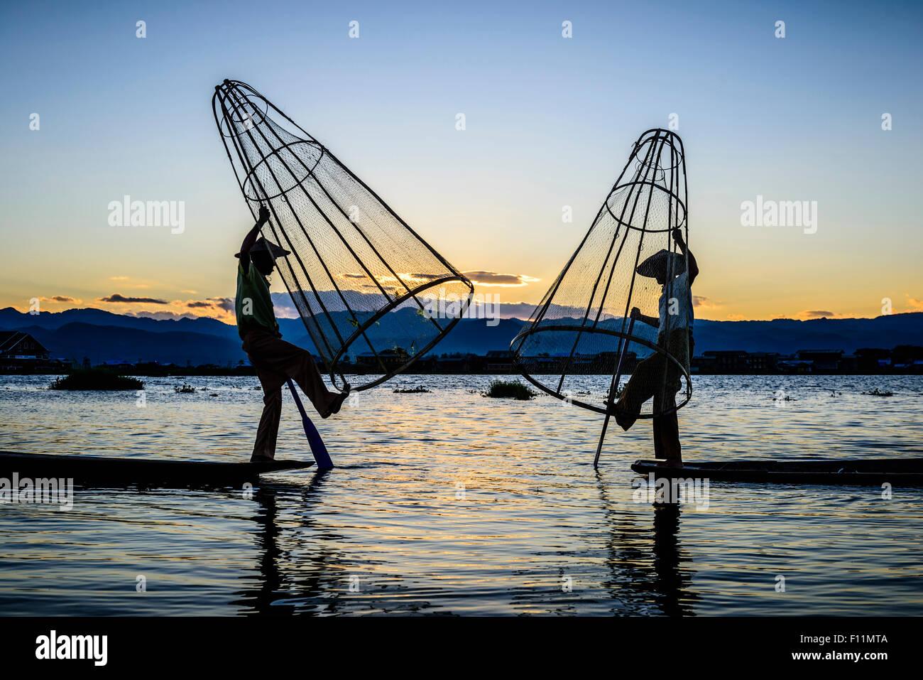 Asiatische Fischer mit Fischernetzen im Kanu auf dem Fluss Stockbild