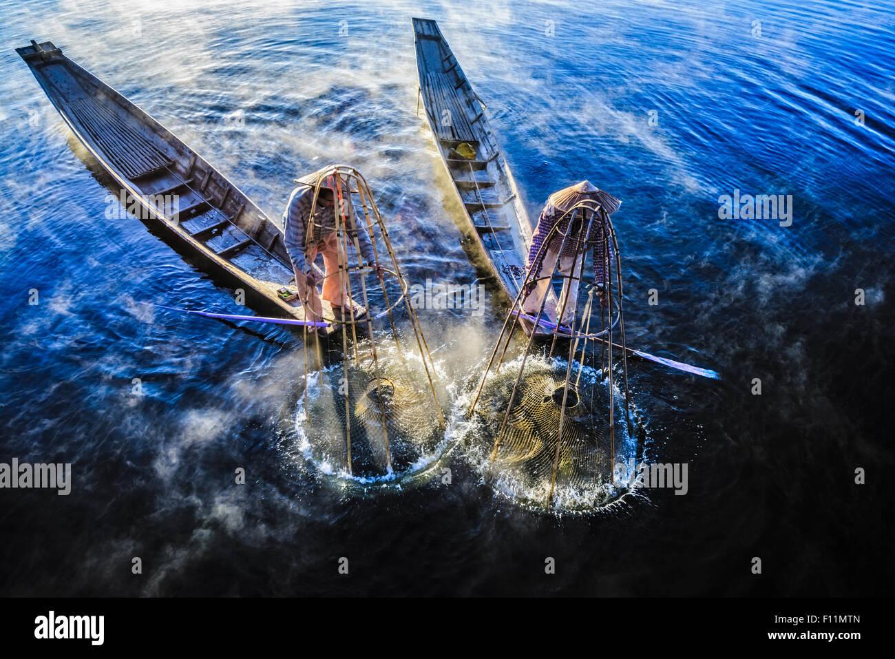 Erhöhte Ansicht der asiatischen Fischer mit Fischernetz in Kanus am Fluss Stockbild