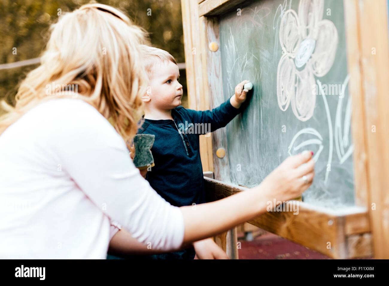 Schöne Mutter und Sohn auf Tafel mit Kreide zeichnen Stockbild