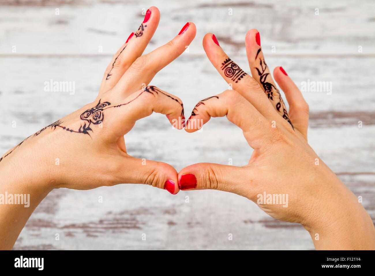 Frau Hände mit Nagellack lackiert mit schwarzen Henna tun Herz Geste ...