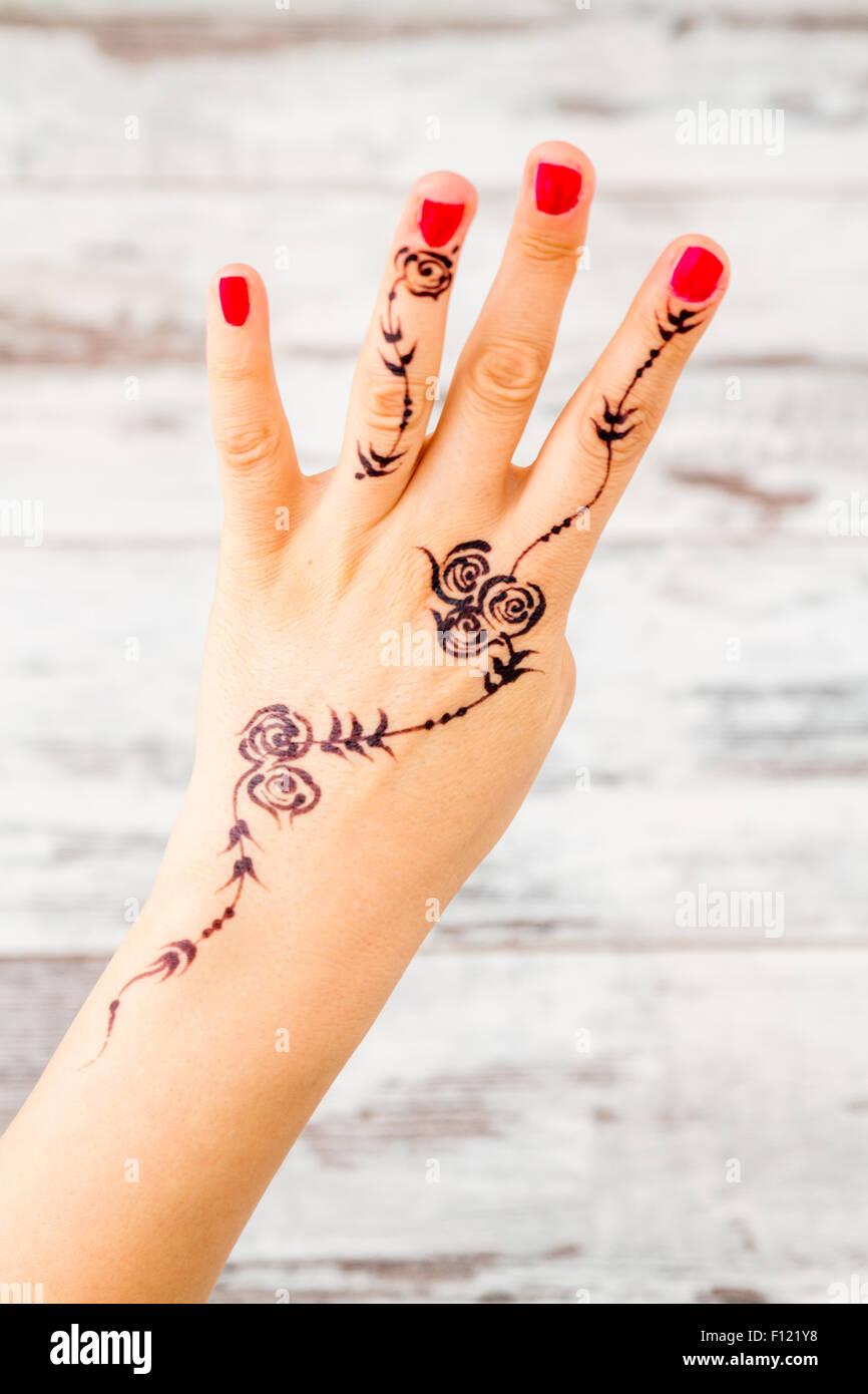 Frau Hand mit Nagellack lackiert mit schwarzen Henna Zahlen zählen ...