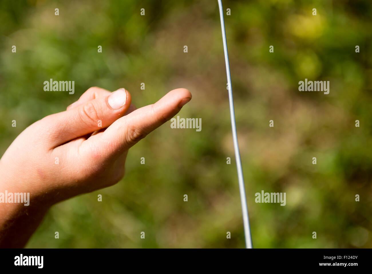 Kinderhand berühren Elektrozaun Draht auf der Weide, Vieh zu ...