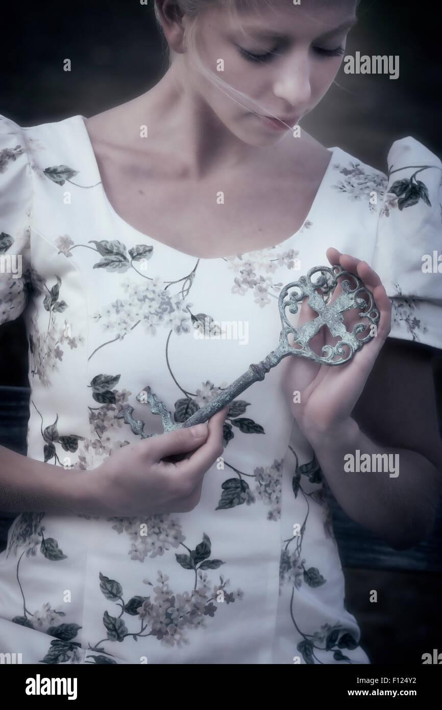 eine Frau hält einen großen, alten Schlüssel in ihren Händen Stockbild