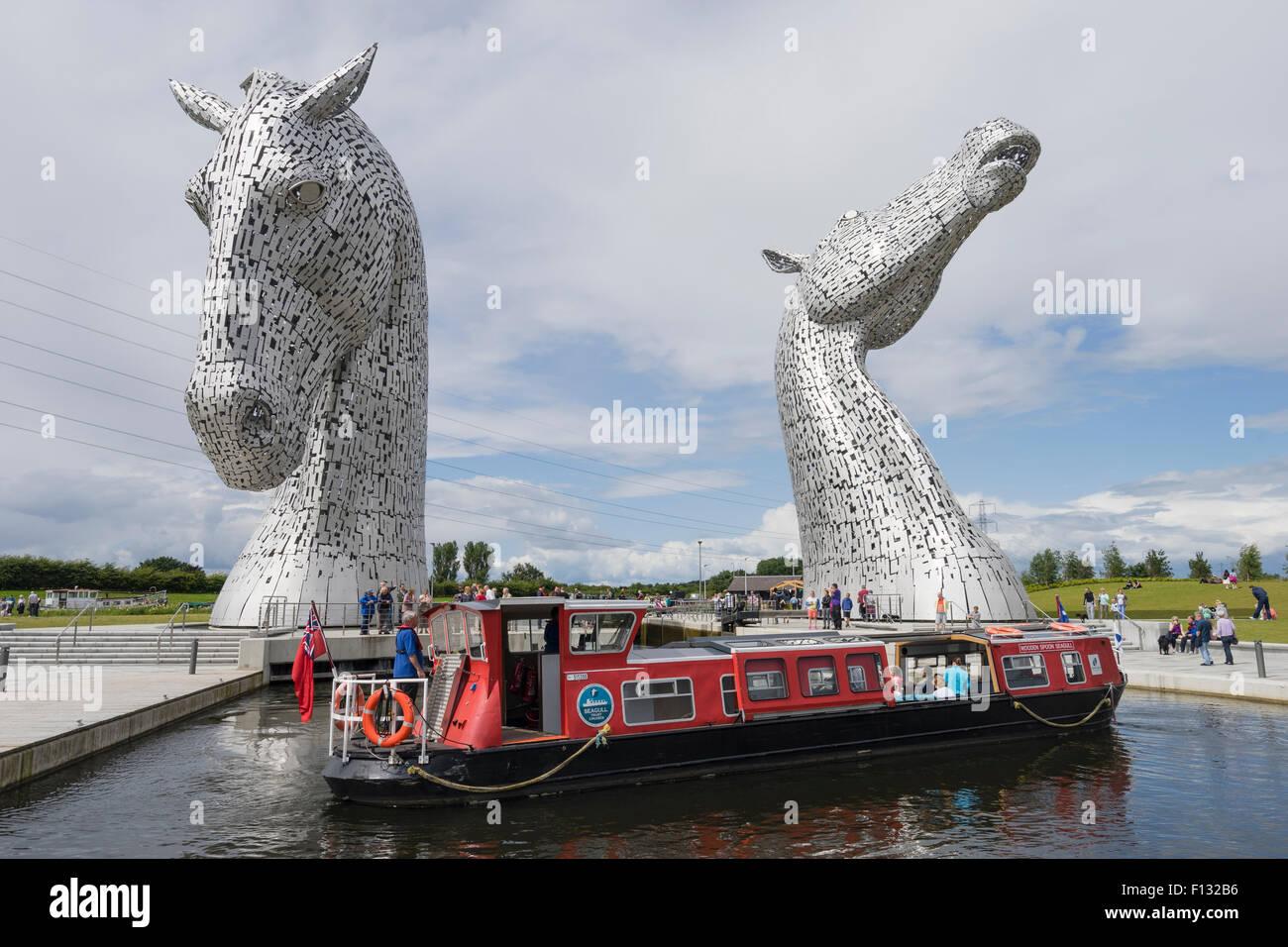 Die Kelpies Skulptur von zwei Pferden überqueren Forth und Clyde Canal und touristischen Kanalboot im The Helix Stockbild