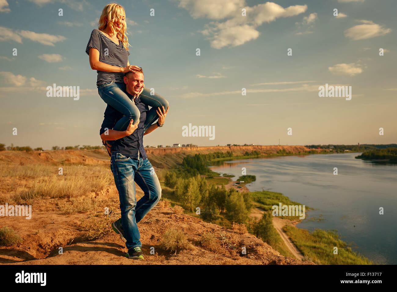 Liebespaar am Ufer Flusses. Mann mit Mädchen auf Huckepack. Sommertag. Das Konzept einer romantischen Beziehung. Stockbild