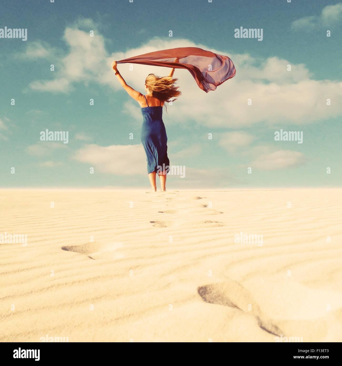 Rückansicht einer Frau mit einem Schal, der im Wind weht Stockbild