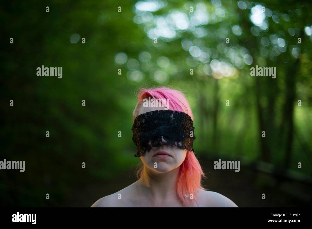 Der Stoff, aus dem Alpträume: eine Frau mit gefärbten roten Haaren mit verbundenen Augen allein im Freien Stockbild