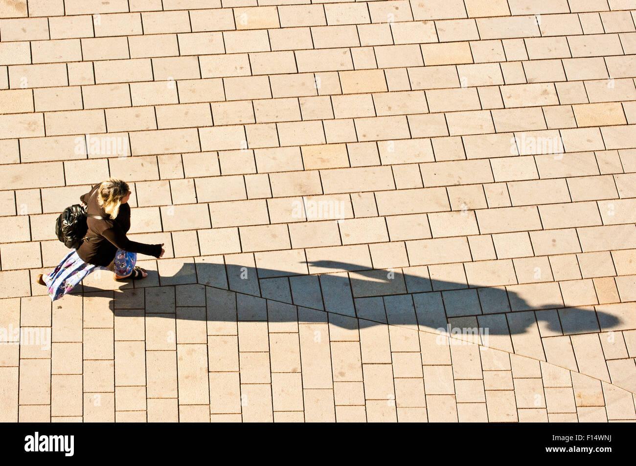 Frau auf der Straße, einen langen Schatten zu projizieren. Von oben gesehen Stockbild