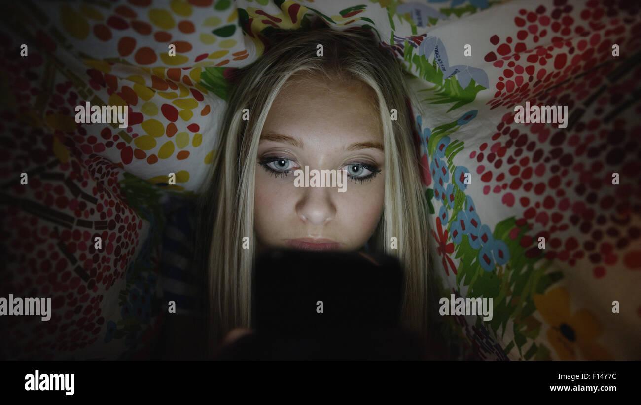 Niedrigen Winkel Blick auf neugierige Mädchen heimlich mit Handy unter Decke in der Nacht Stockbild