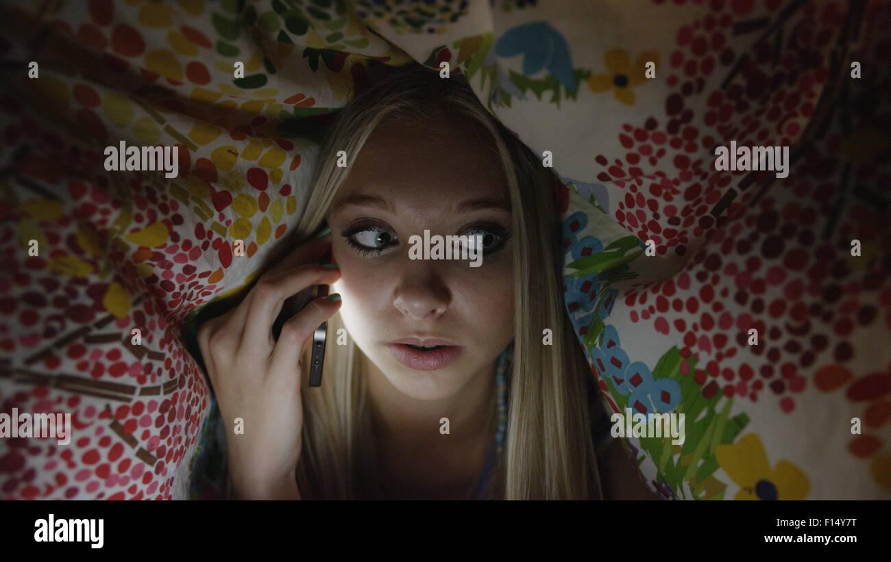 Niedrigen Winkel Blick auf neugierige Mädchen heimlich reden über Handy unter Decke in der Nacht Stockbild