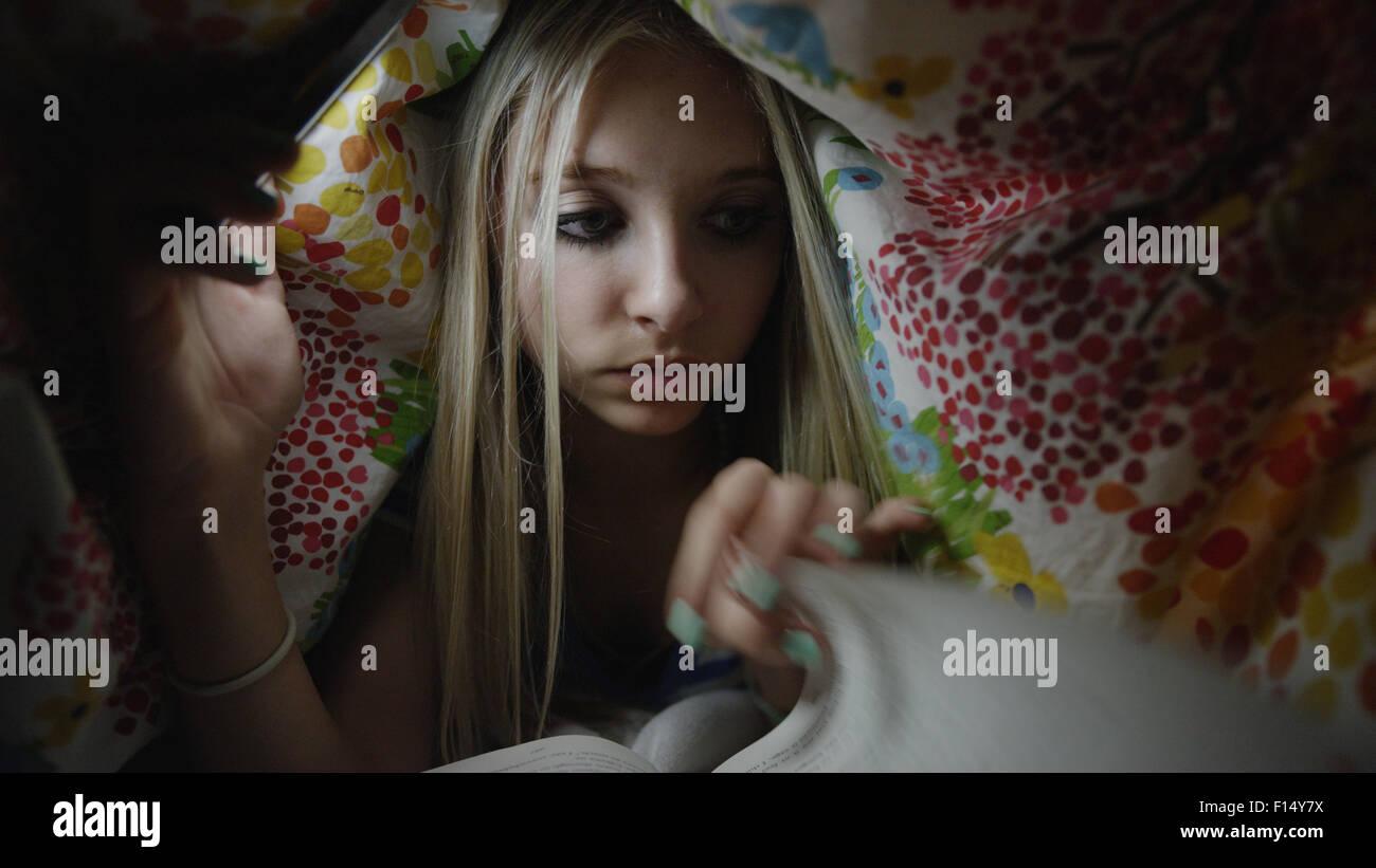 Niedrigen Winkel Blick auf neugierige Mädchen heimlich mit Hilfe von Handy-Licht und Buch unter Decke in der Stockbild
