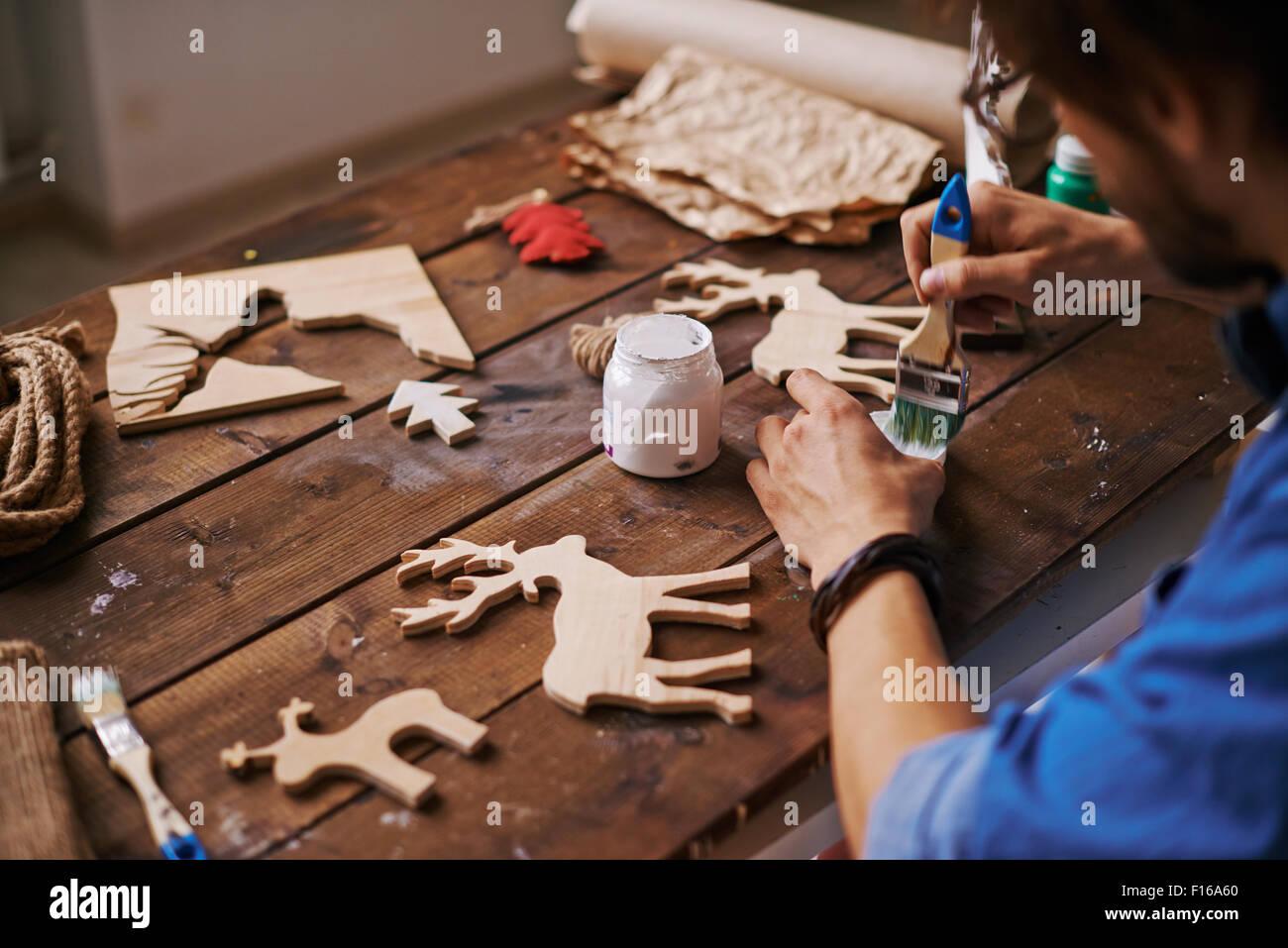 Junge Handwerker mit Paintbrush Xmas Hirsch mit weißen Gouache Malerei Stockbild