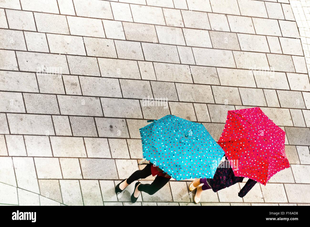 zwei Frauen unter ihren Regenschirmen, von oben gesehen Stockbild