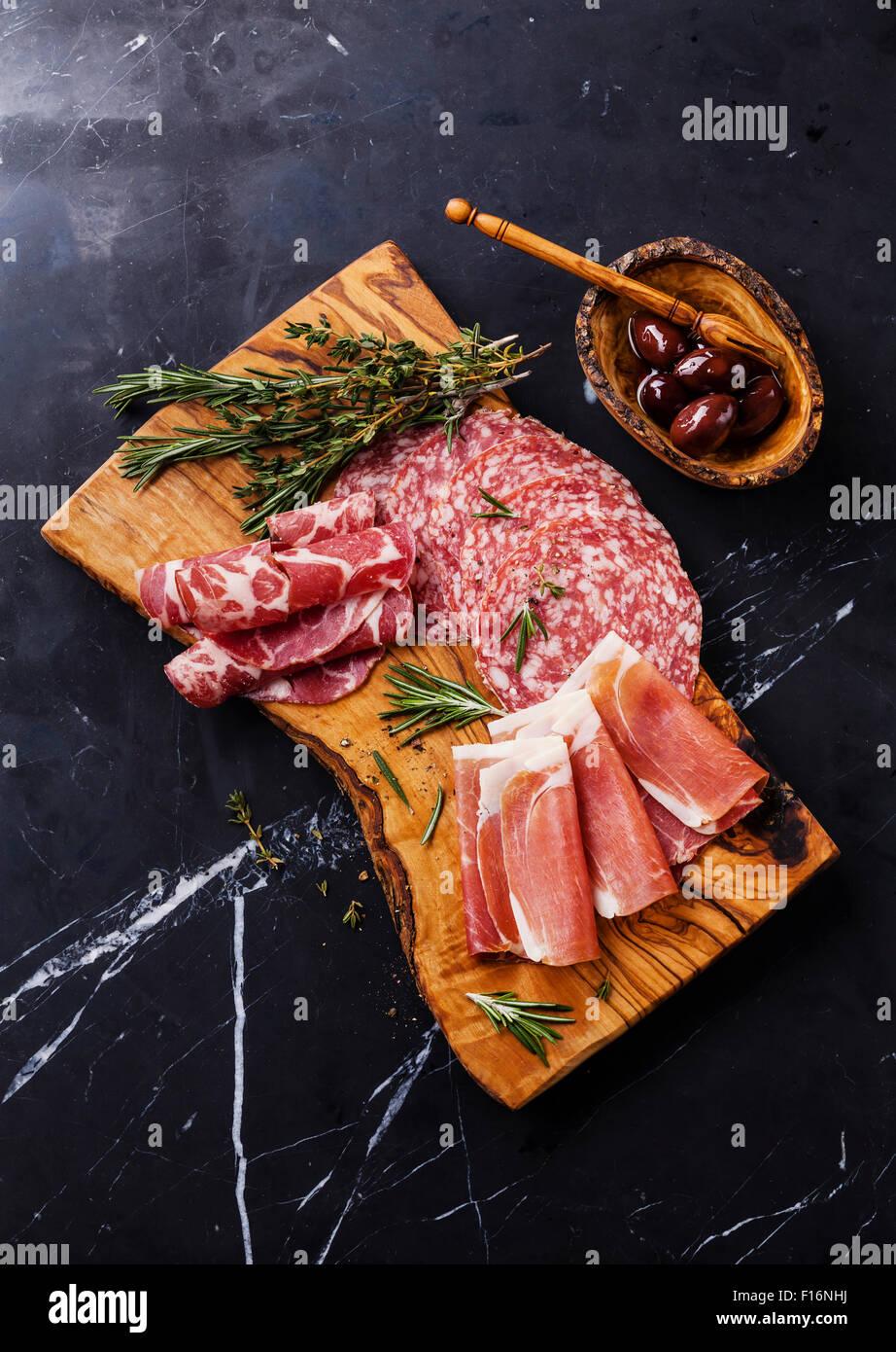 In Scheiben Prosciutto di Parma auf Holzbrett mit Salami und Rosmarin auf schwarzem Marmor Hintergrund Stockbild