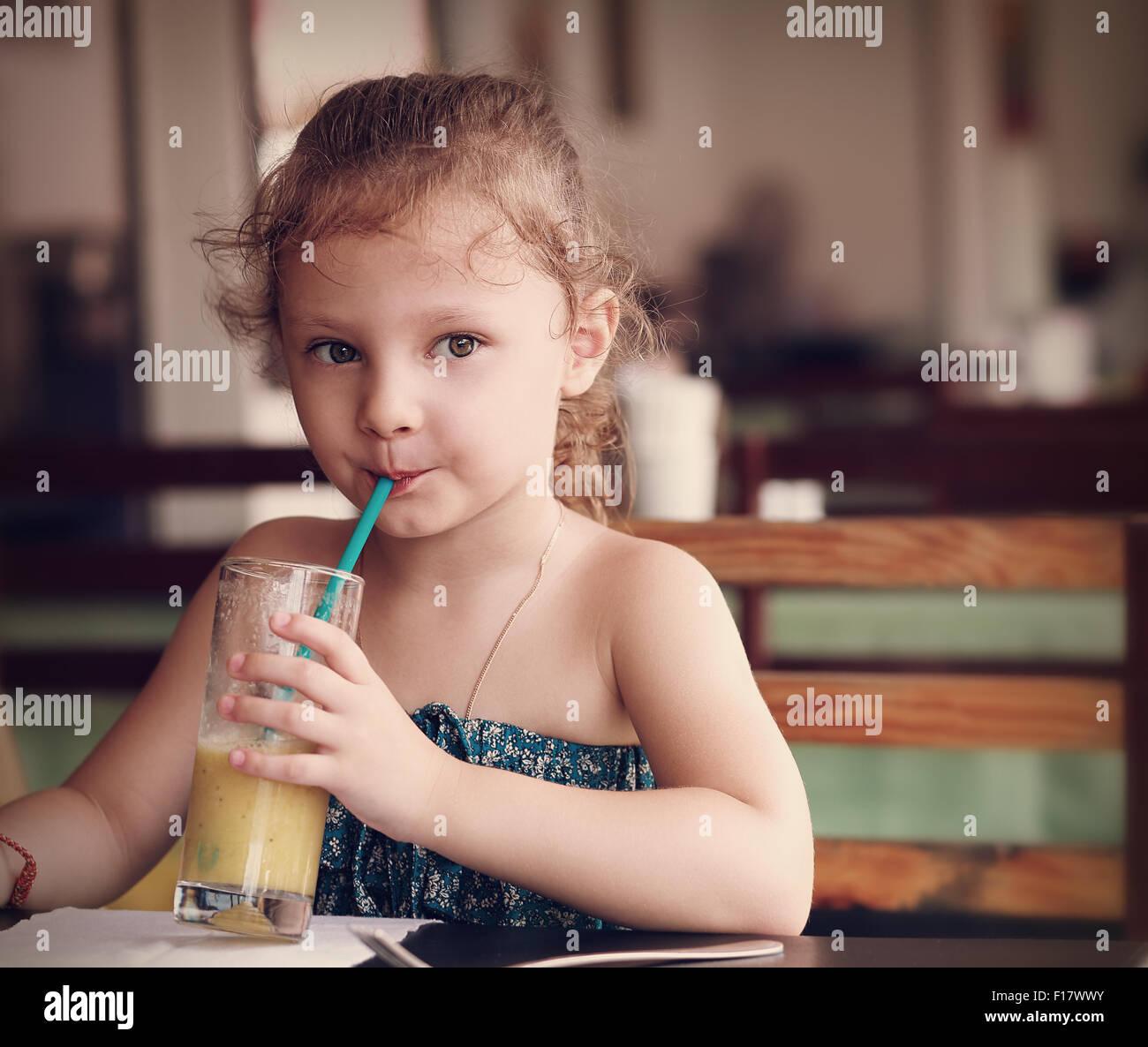 Niedliche denken Kind Mädchen trinken Saft im Café mit ernsten Blick. Closeup portrait Stockbild